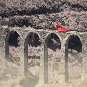 Woman in red dress walking on the edge of an aqueduct