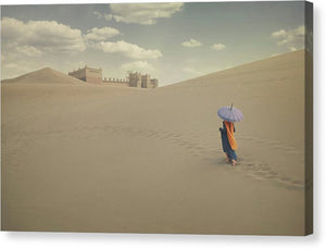 Bedouin woman in a blue dress and with purple umbrella walking towards a town in the desert