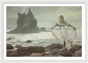 Young blonde woman standing on a rock in sea and holding her dress