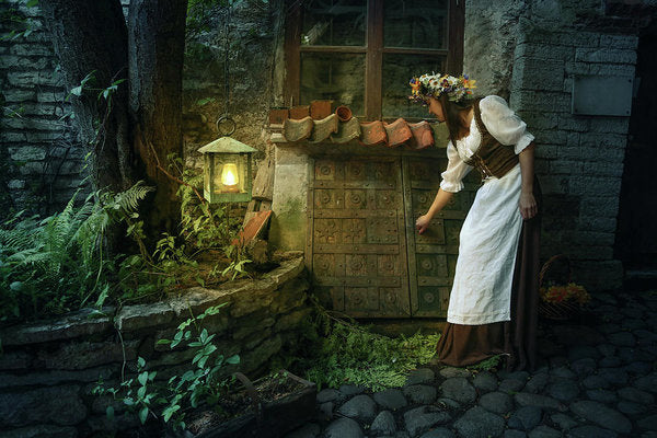 Peasant woman in medieval dress opens a cellar door at night