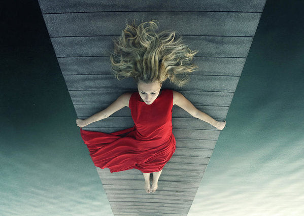 Young woman in red dress laying on pier upside down