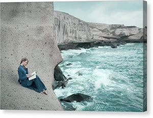 Woman in a long blue dress reading book on the cliff by the ocean. Tajao, Tenerife, Canary islands