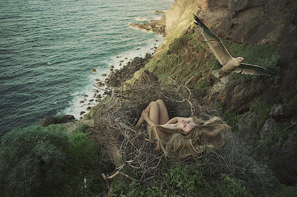 Woman with a long blonde hair sitting in a bird-nest near the sea