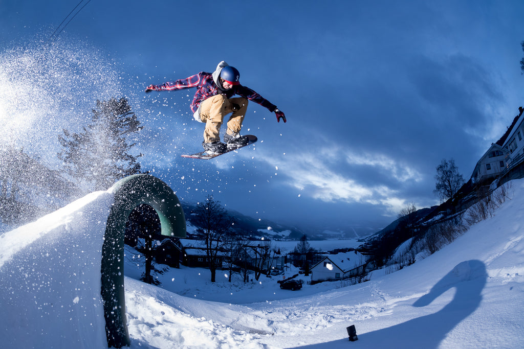 Snowboarder hitting a jump at dusk. Photo by Carl Van den boom
