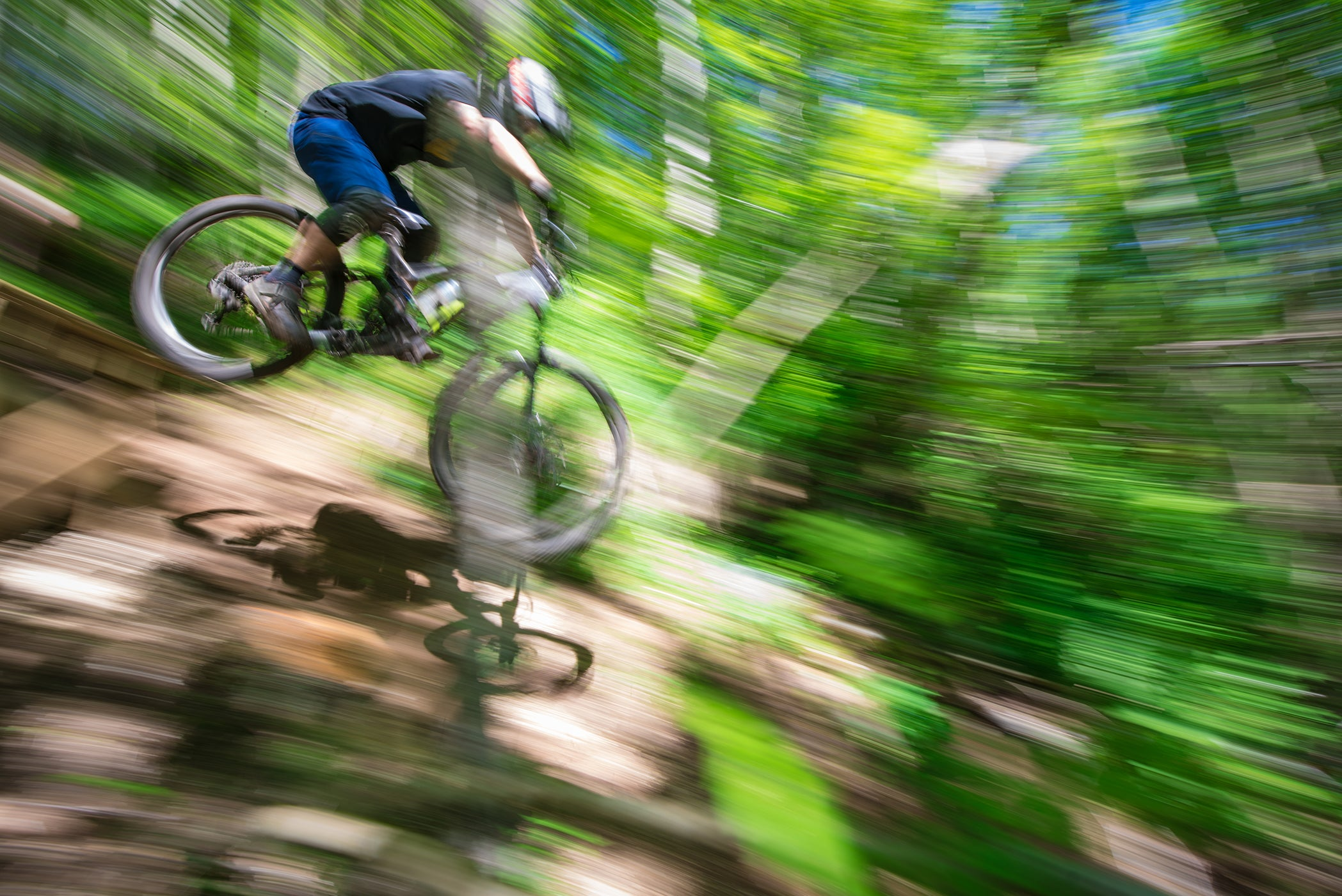 Mountain Biker riding downhill through green forest