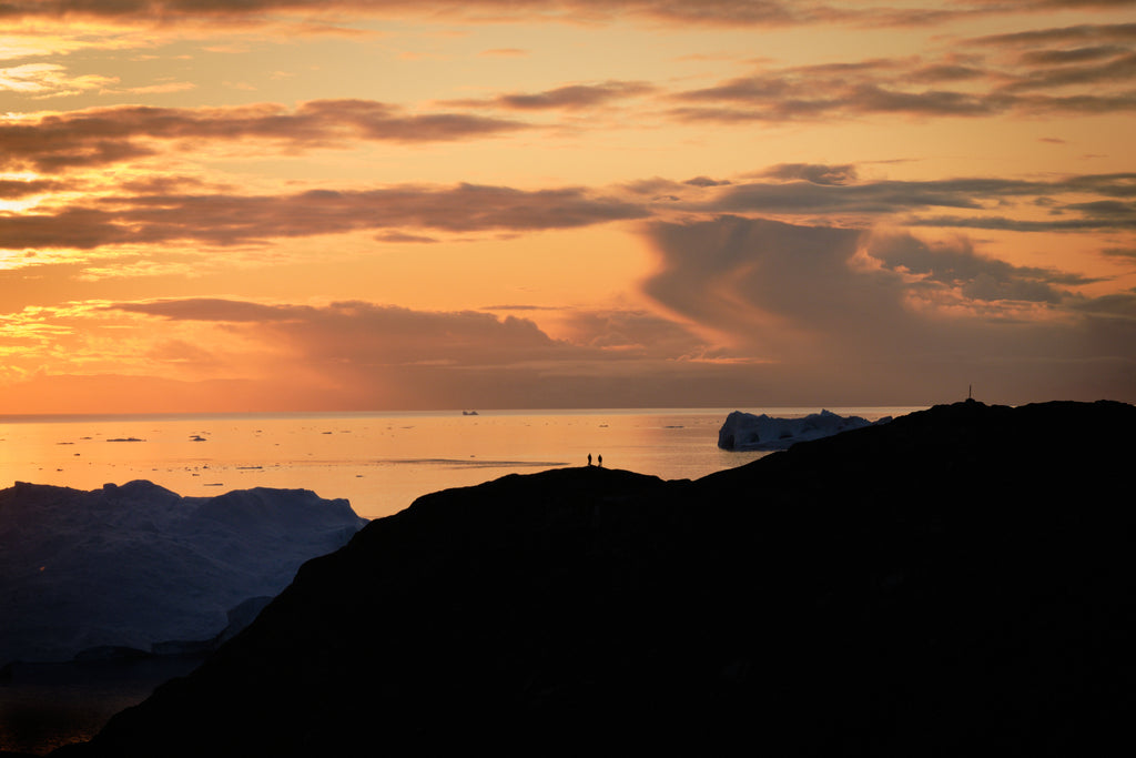 silhouettes in an orange sky in greenland