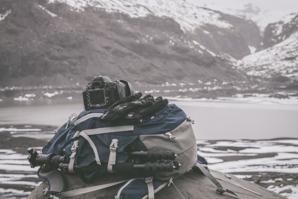 winter photography gear piled up on iceland beach