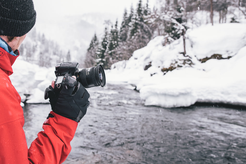 Man with photography gloves holding camera by a snowy river