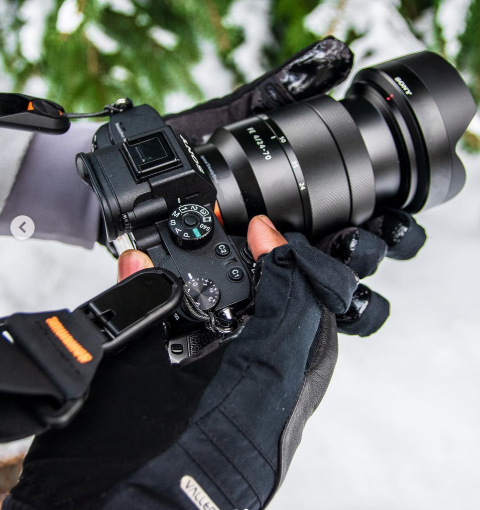 Photography gloves holding a camera in the snow