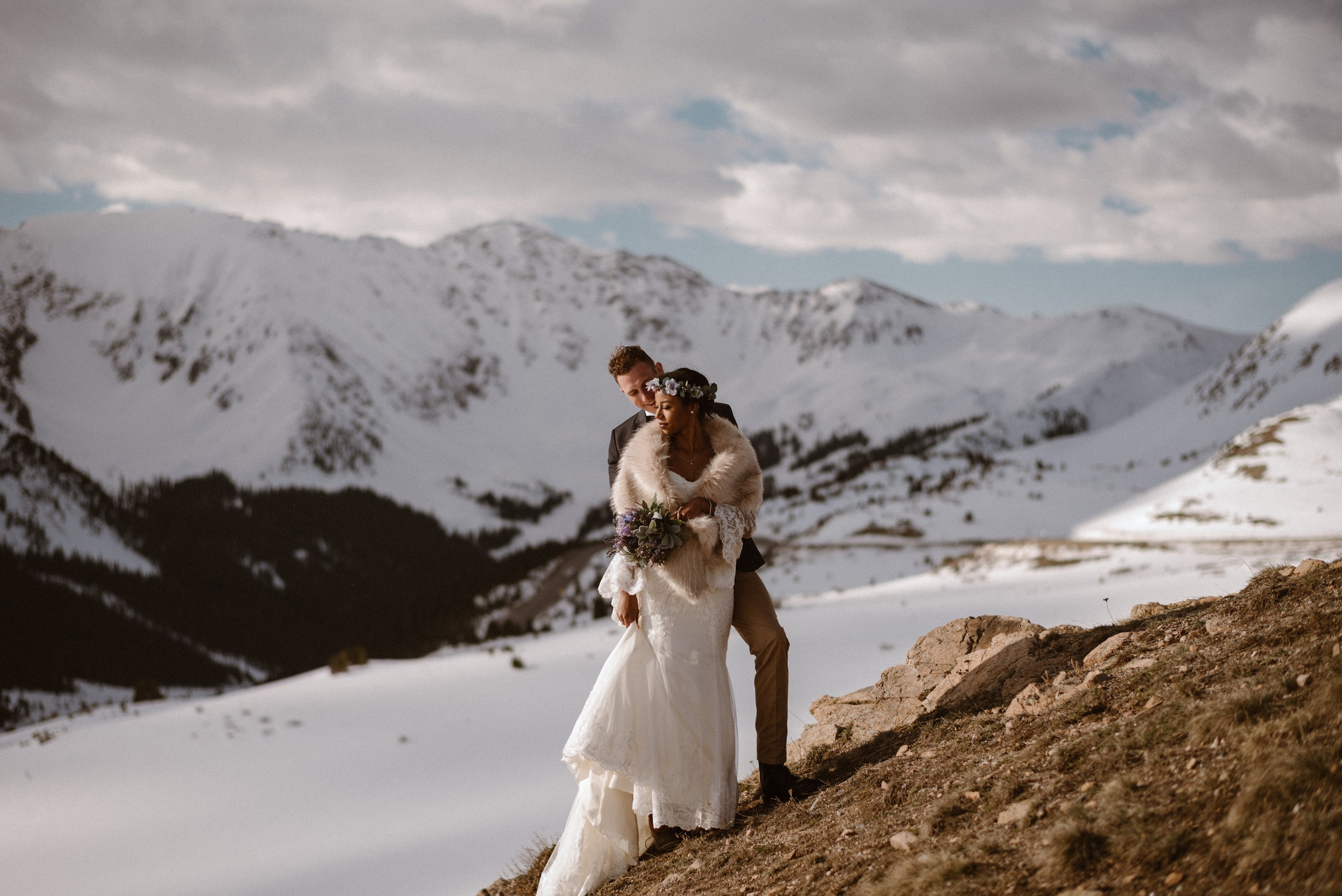 Bride and groom on snowy mountain