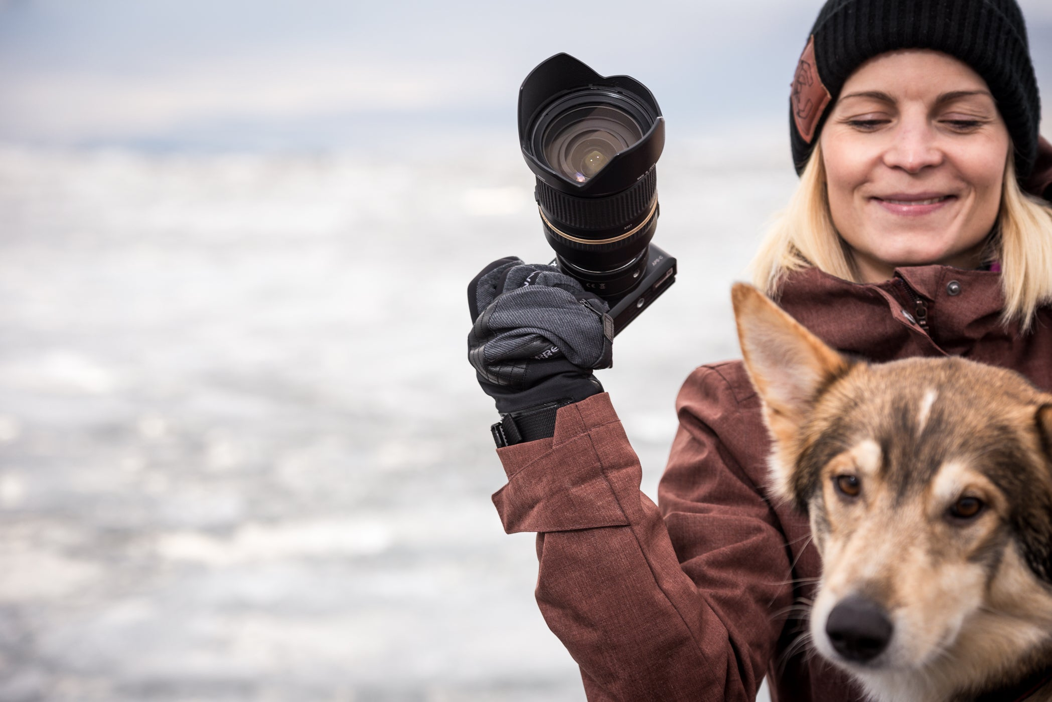 Woman with camera and a dog in the mountains