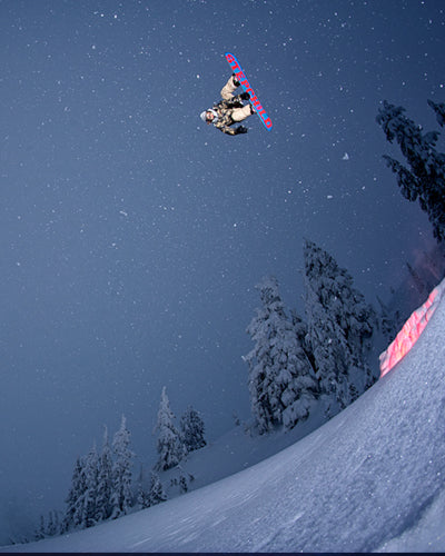 snowboarder jump at night with stars