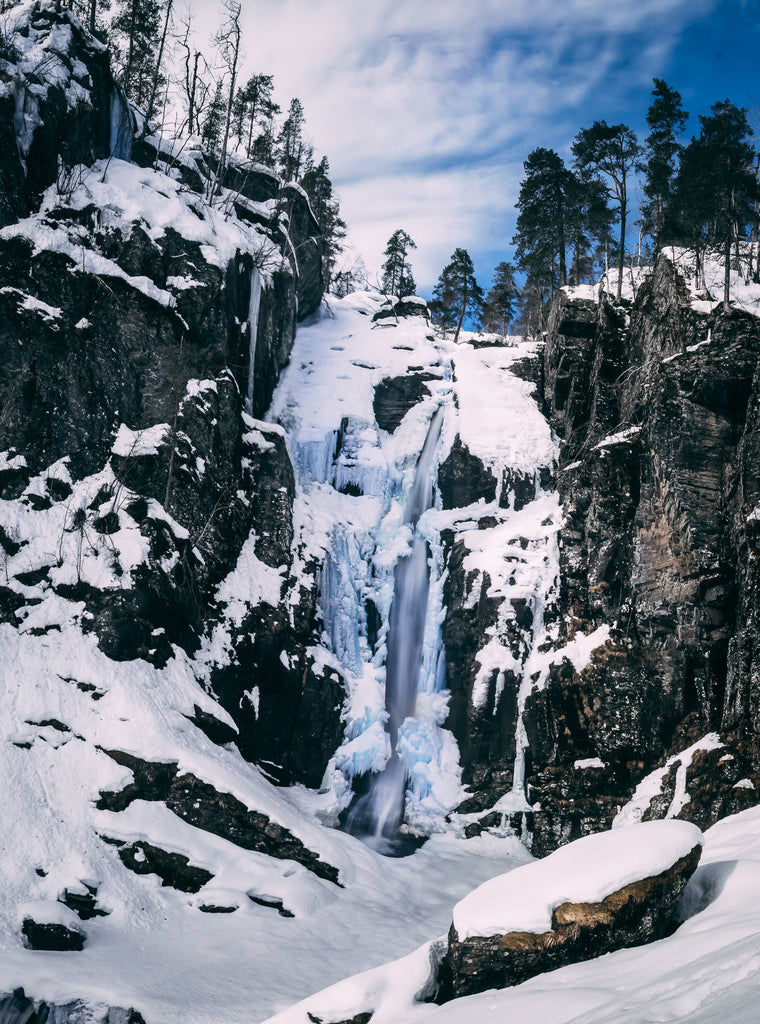 Vertical panorama final image of a waterfall in winter