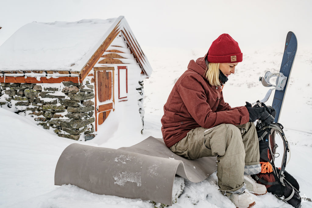 snowboarder sitting outside of snowy cabin holding a camera