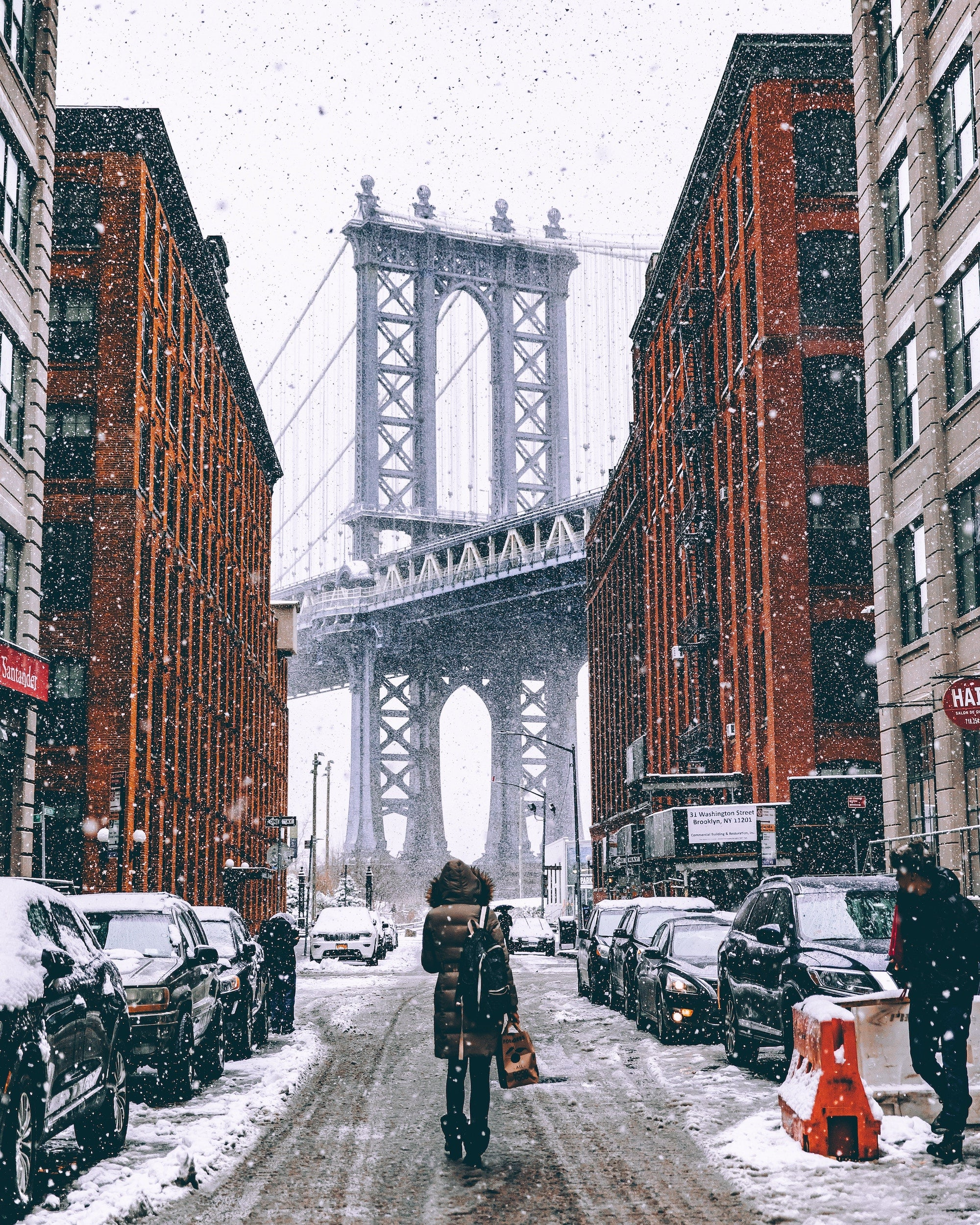 woman standing in the middle of a snowy street with bridge in the background