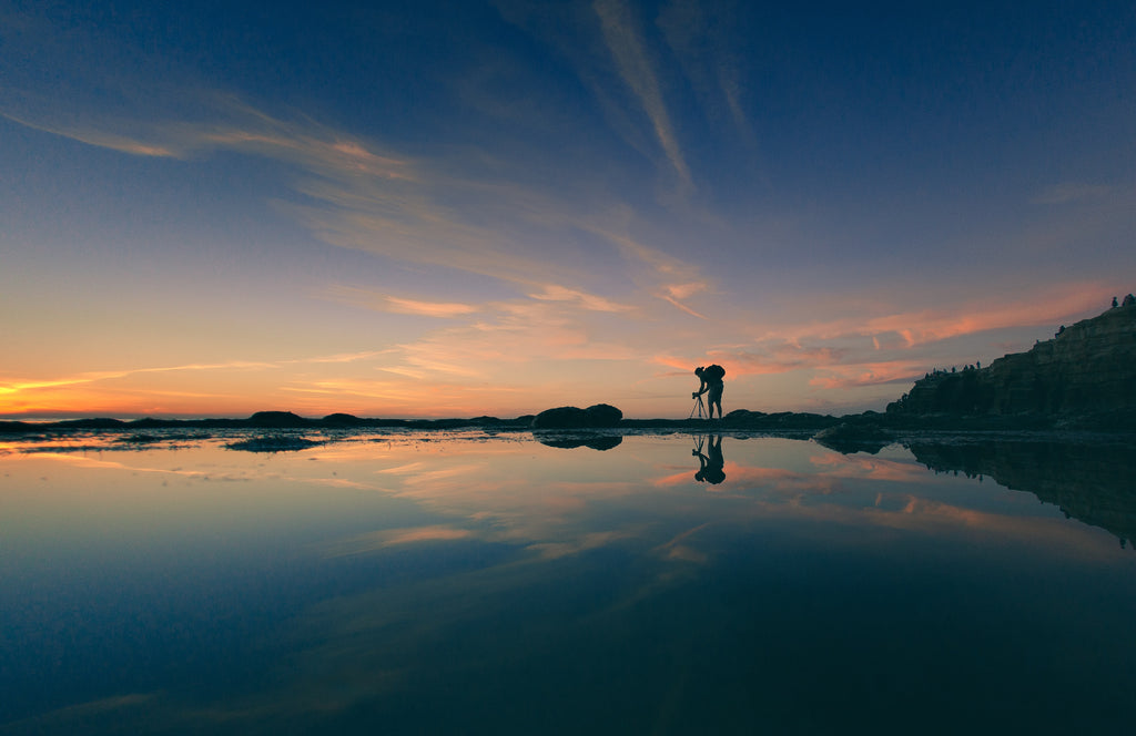 Man adjusting tripod during sunset_Photo by Garrett Patz on Unsplash