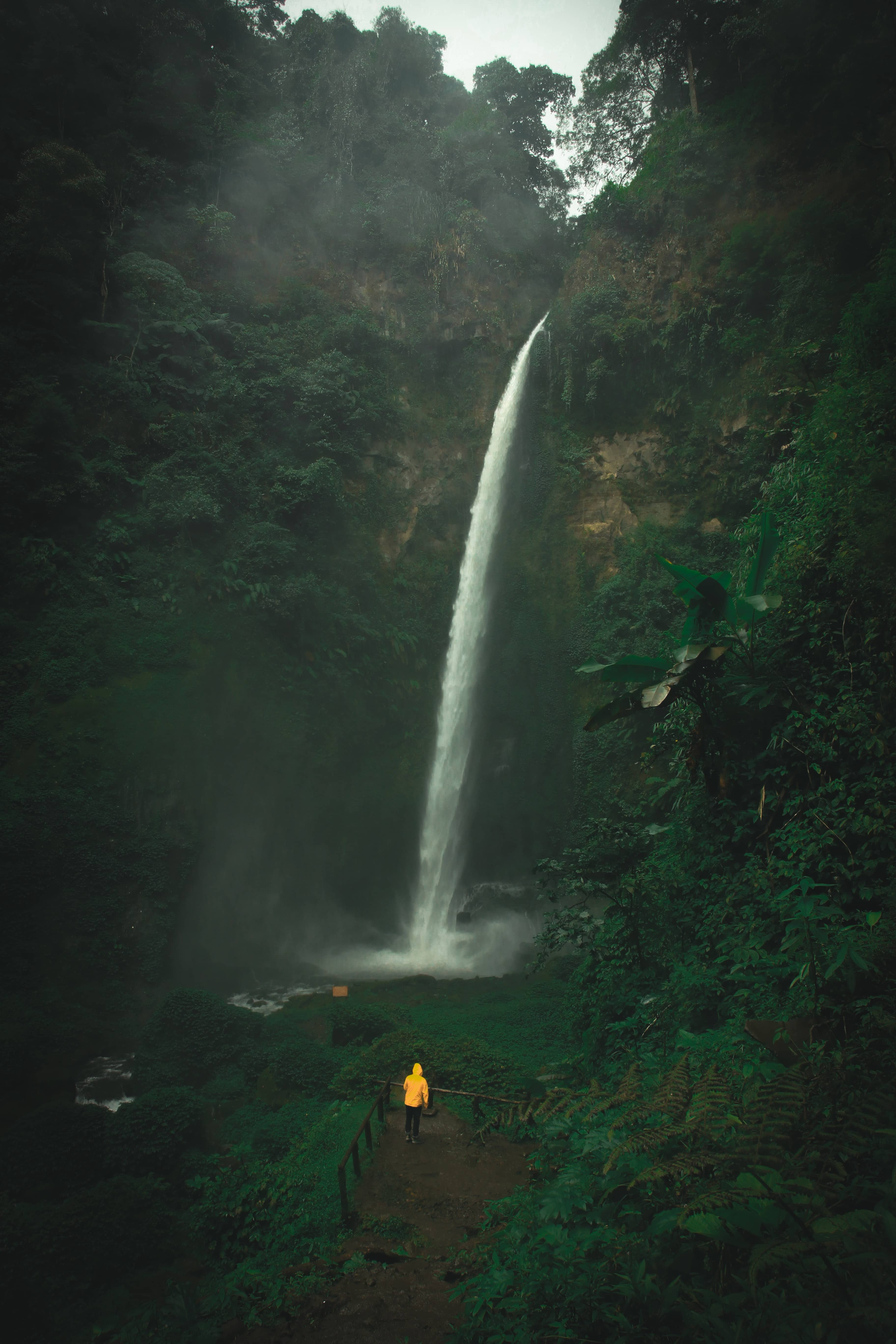 person walking under a water fall in a rainstorm
