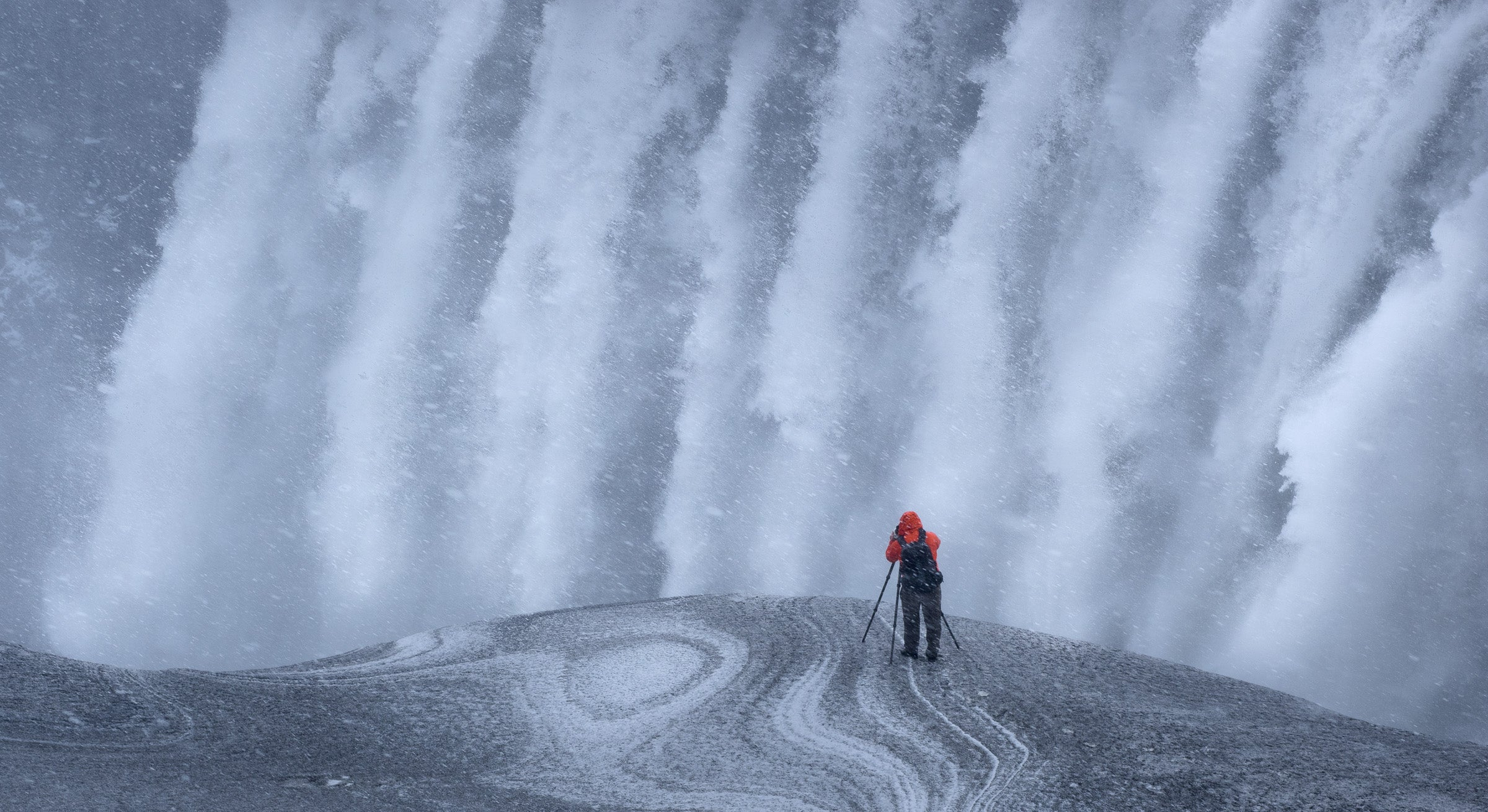 man taking a photo of a waterfall in a snow storm