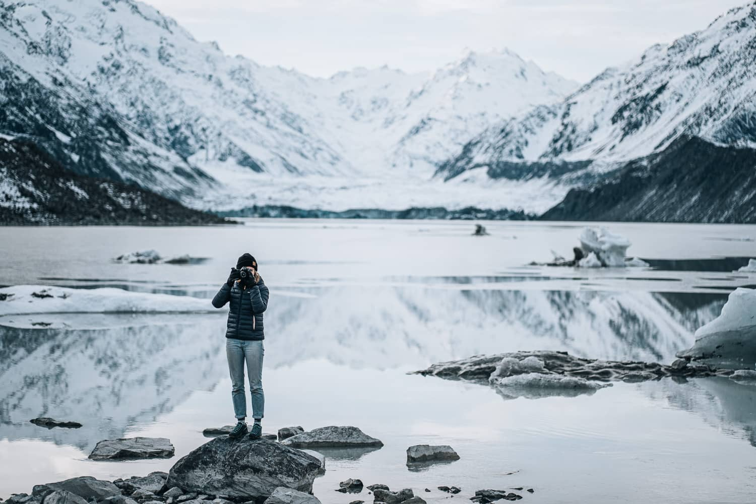woman standing near a glacier taking a photo
