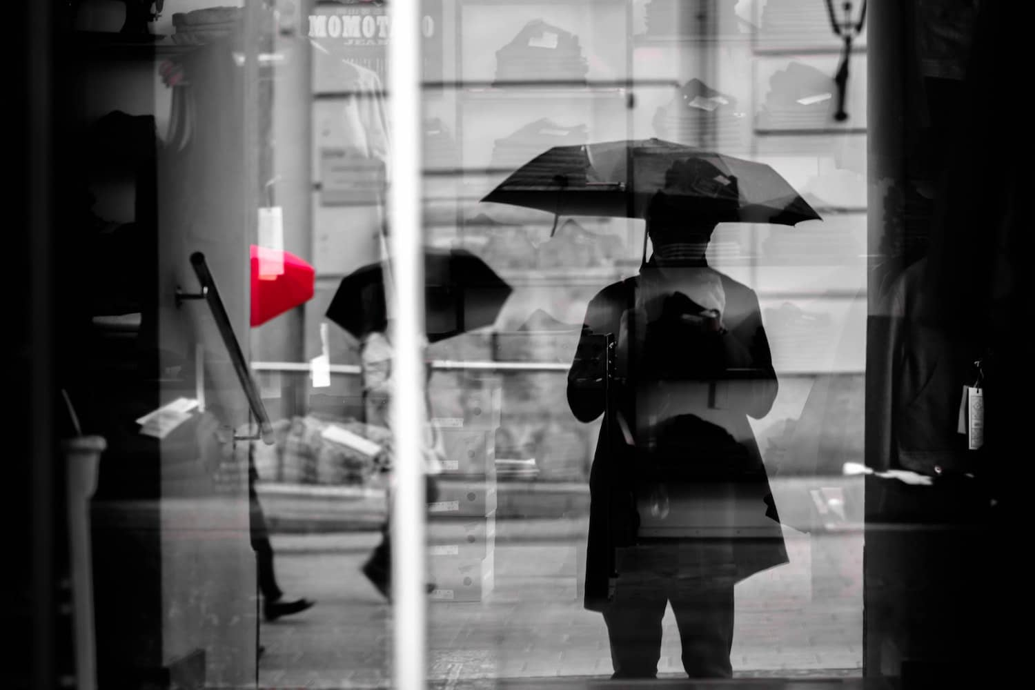 black and white photo of person in the rain with umbrella