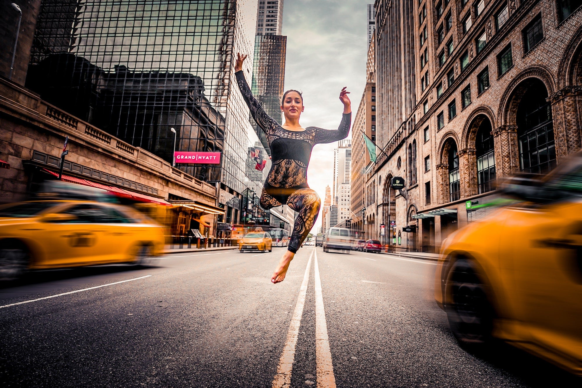 woman jumping in the middle of a busy street