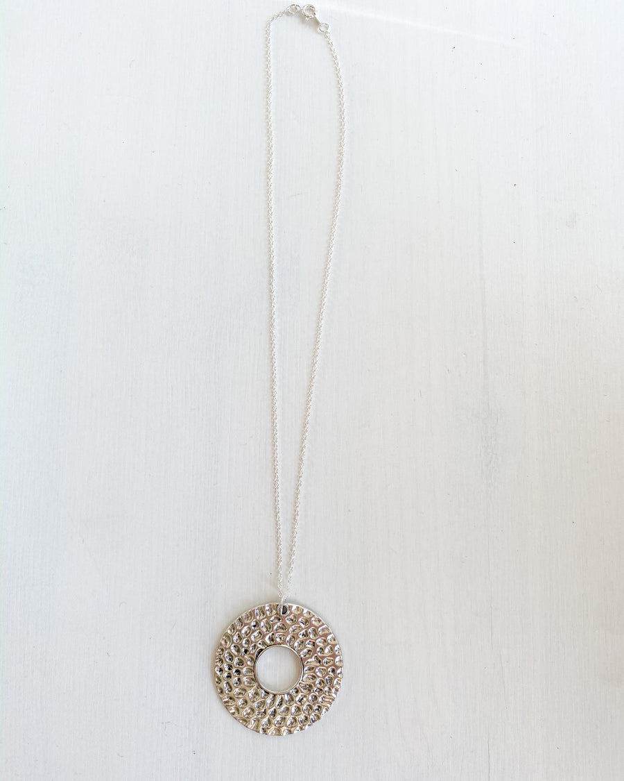 Short silver pendant necklace with hammered metal circle that is handmade from Artisans in India.