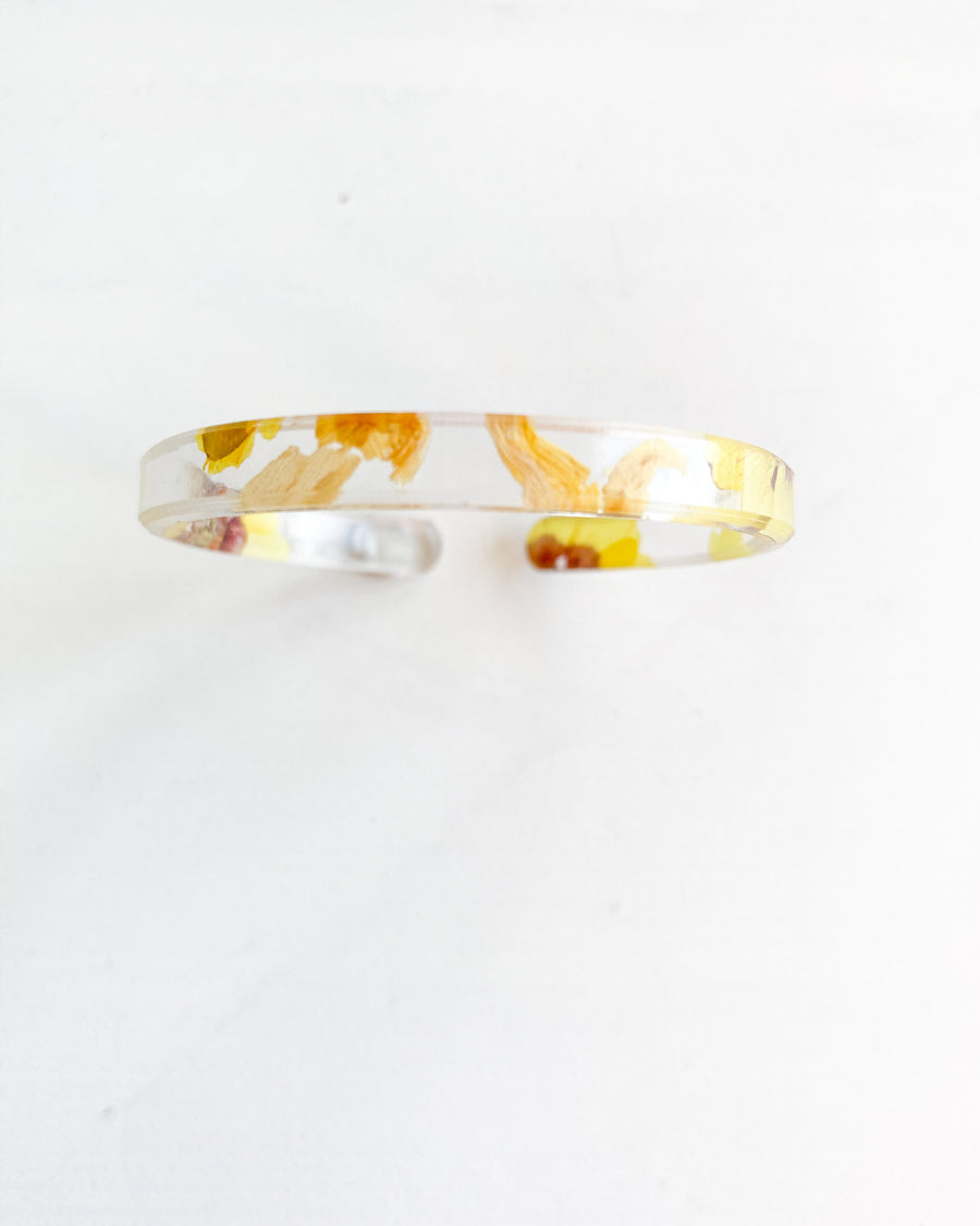 Resin Bracelet with Real Dried Daisy Flowers inside. It's bright yellow flowers that you can see through the resin, and very light weight to wear.