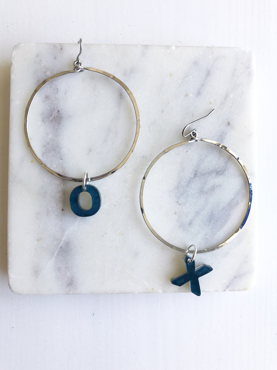 Silver Hoop Earrings, one hoop earring has a letter X charm made from resin hanging from right hoop earring, and the other left hoop earring having the letter O charm hanging from it.