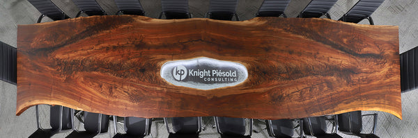 Claro Walnut live edge table photo from above show lit LED branding piece