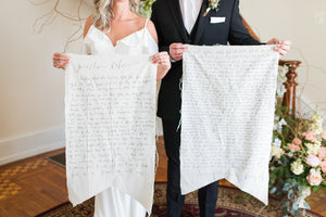 Bride and Groom holding custom vow canvas banners from Handstolearn