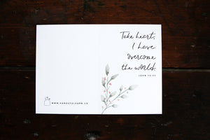 White greeting card with watercolored greenery and the verse: Take heart, I have overcome the world. John 16:33