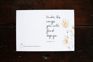 White greeting card with a yellow watercolored flower and the verse: Under His wings you will find refuge. Psalm 91:4