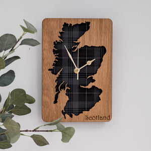 Wooden square wall clock with a cut out map of Scotland. It has a grey tartan background.