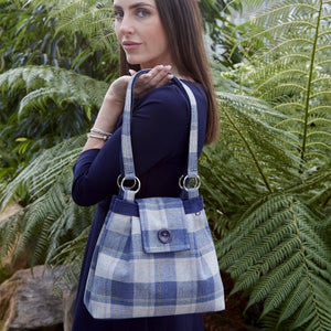 Woman holding an Earth Squared tweed ava bag in blue tartan colour.