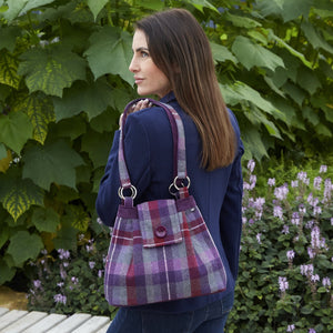 Woman holding an earth squared tweed ava bag in purple and red tartan.