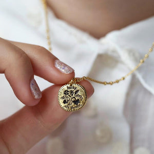 Close up of a woman holding a gold lucky sixpence necklace.