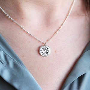 Woman wearing a sterling silver lucky sixpence necklace.