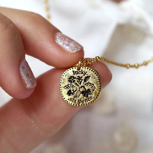 Close up of a women holding a gold lucky sixpence pendant.