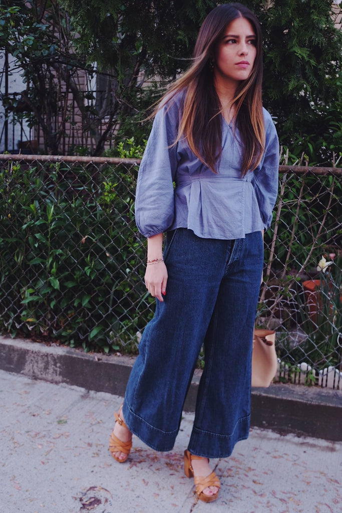 Girl in light purple wrap blouse, wide leg denim, and brown sandals.