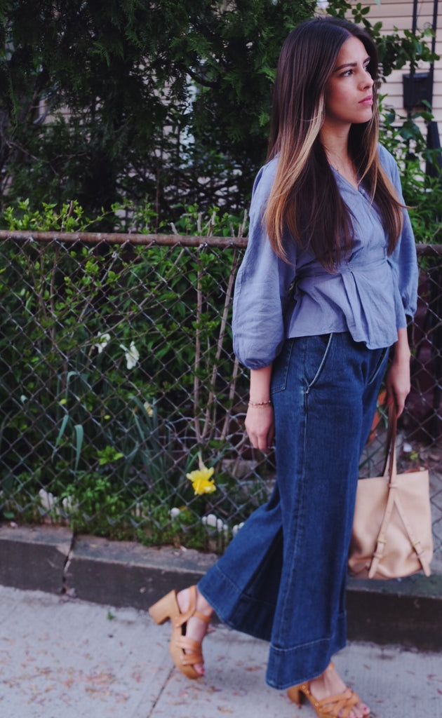 Girl in light purple wrap blouse and wide leg denim outside.