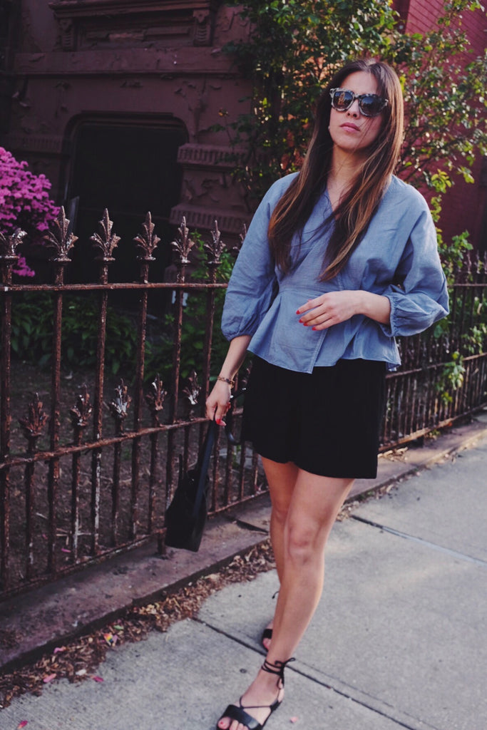 girl in light purple wrap blouse with puff sleeves, black denim shorts, and strappy black sandals in front of an iron gate.