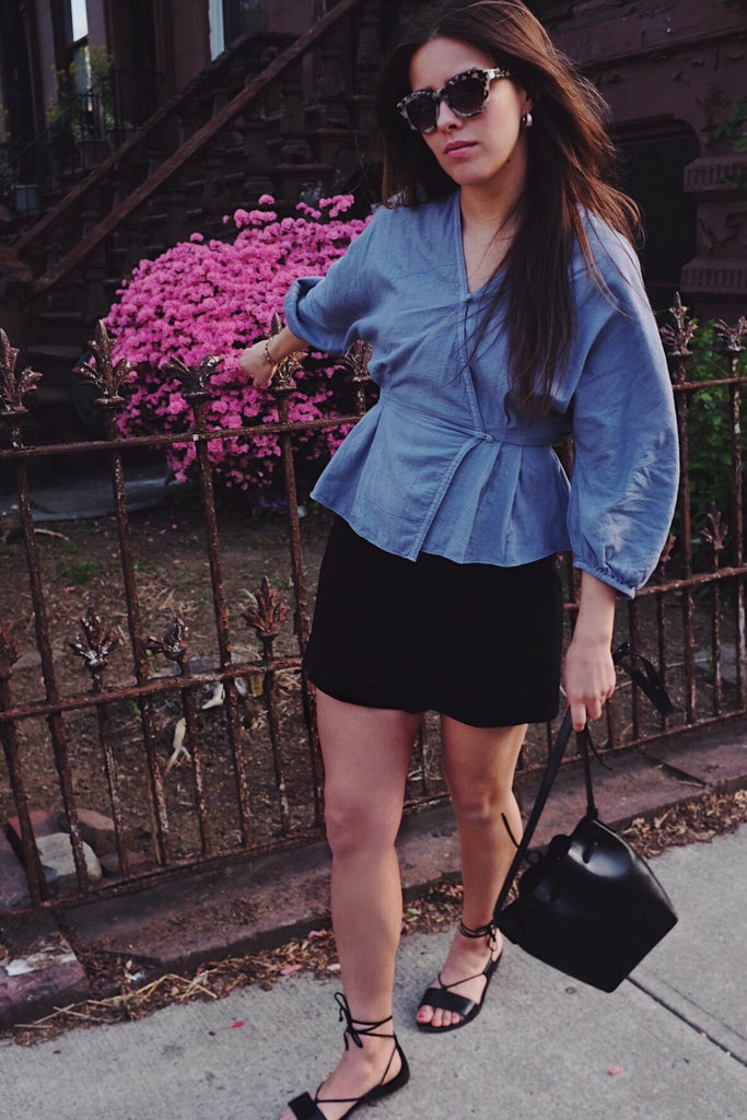 A girl in a light purple wrap blouse with puff sleeves styled with black denim shorts and black strappy sandals.