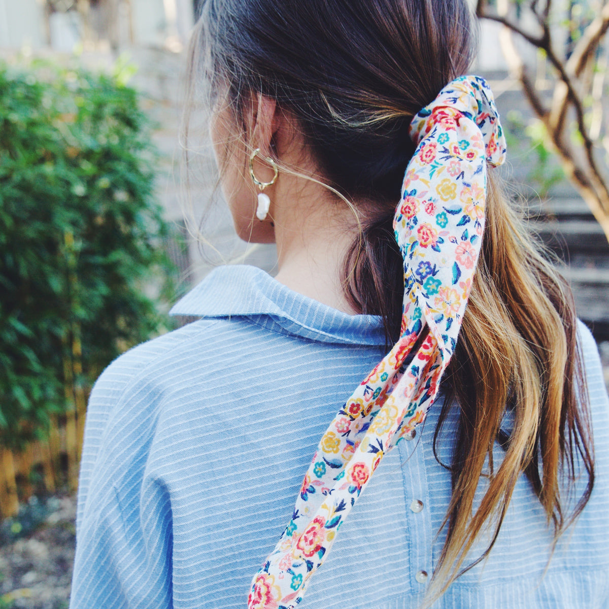 girl wearing blue and white striped shirt, pearl earrings, and a colorful printed hair scarf.