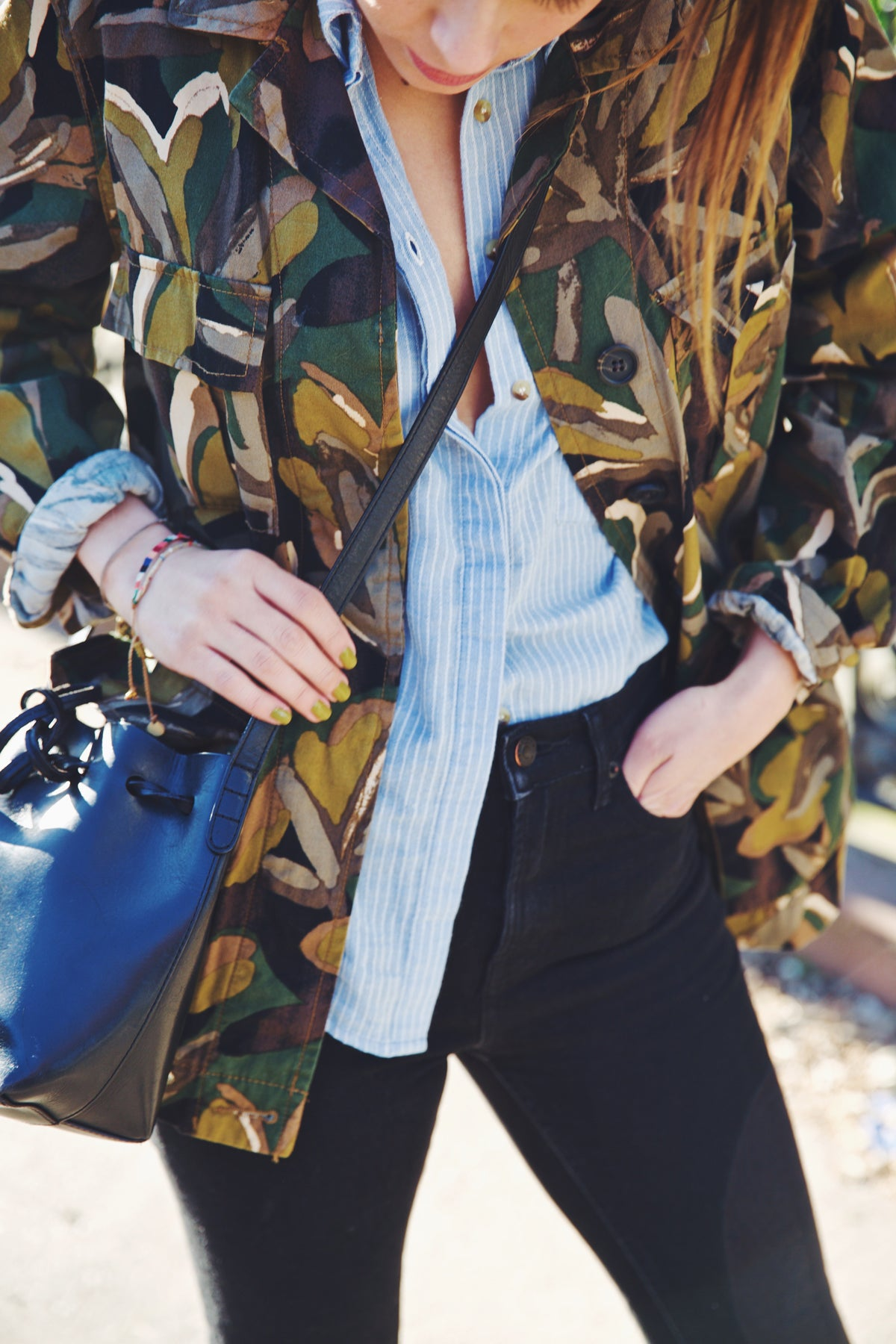 girl wearing camouflage jacket over blue and white striped shirt  with black jeans and black handbag