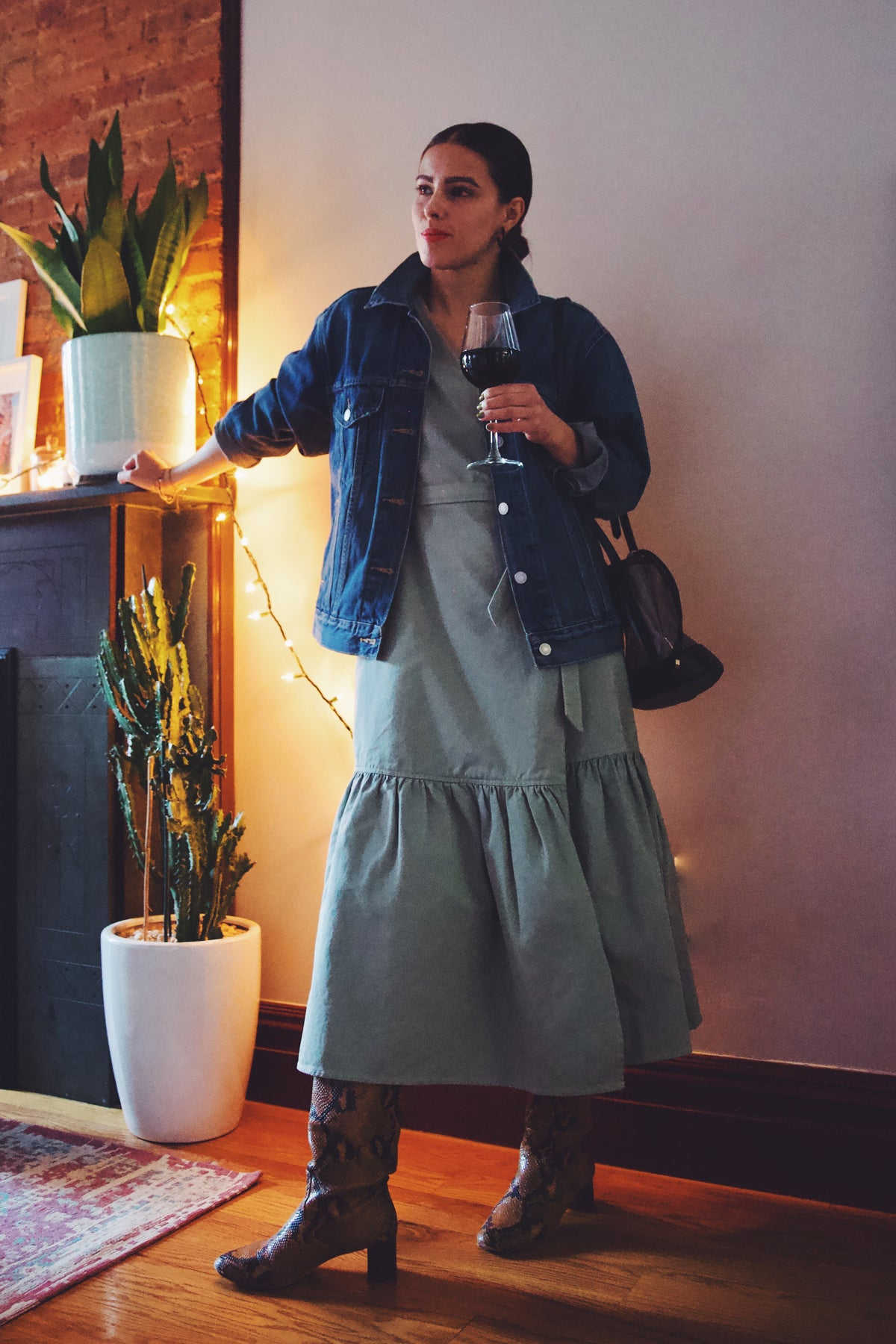 girl wearing ruffle dress with denim jacket and drinking wine