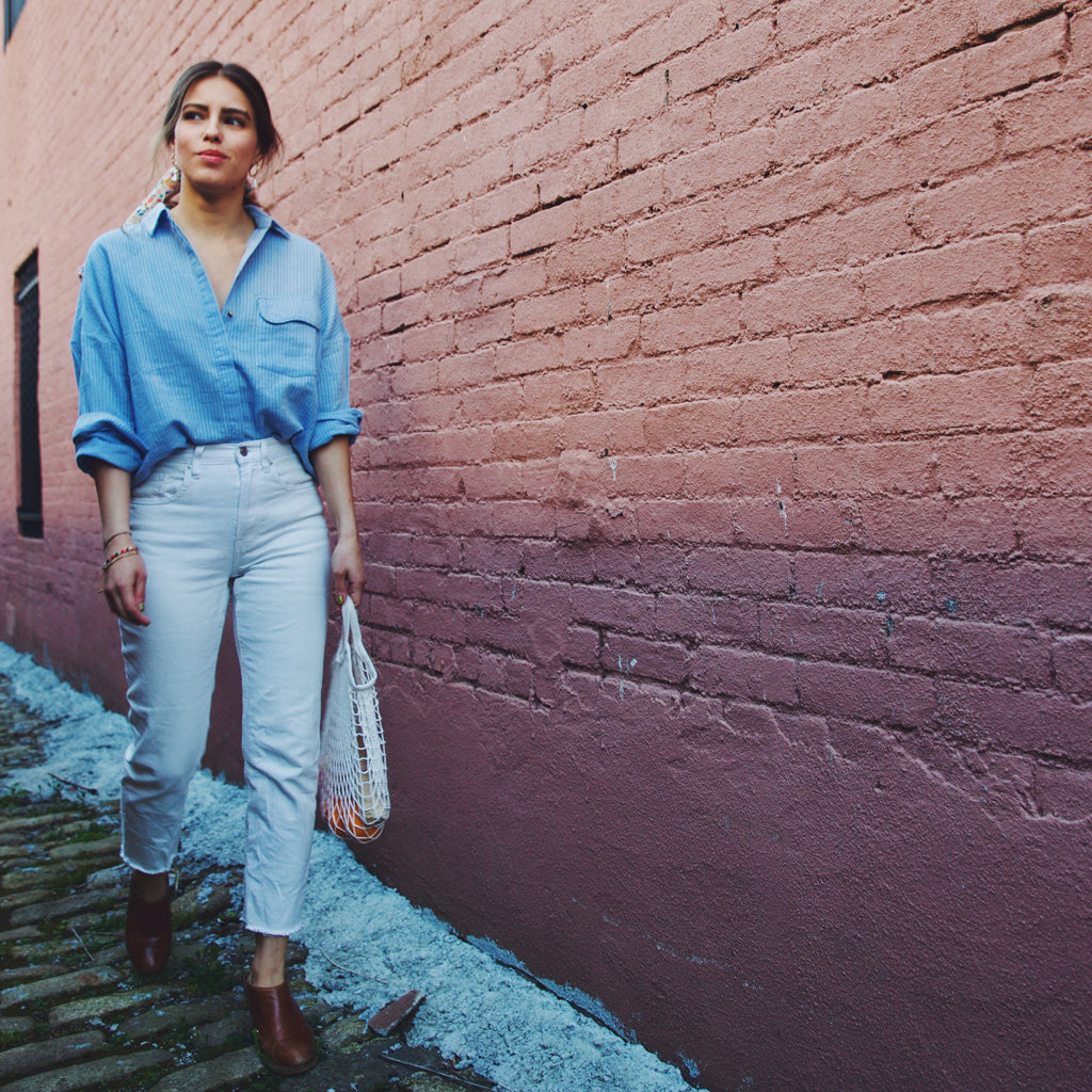 girl wearing blue and white striped shirt and white jeans