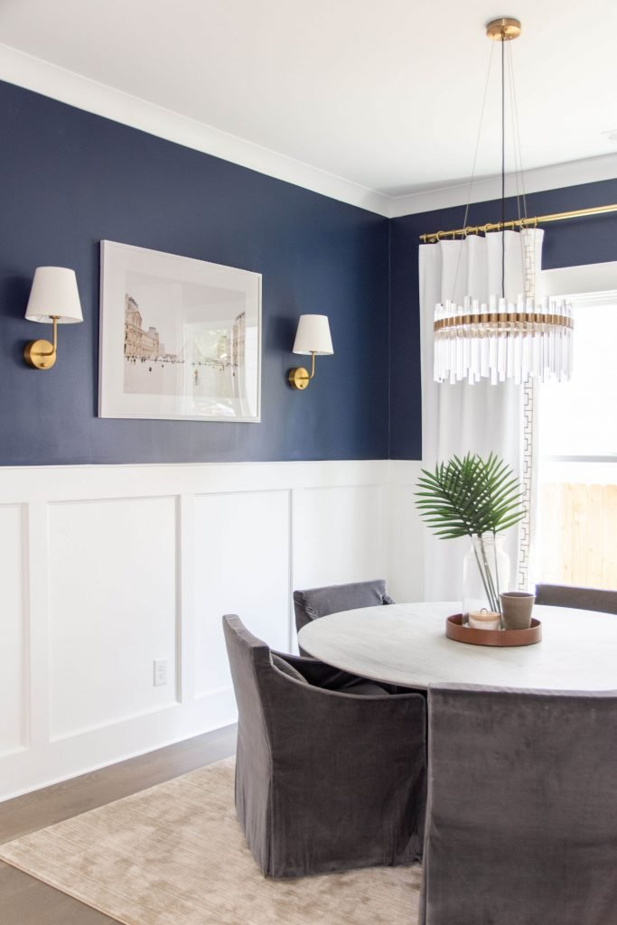 Navy dining room with white chair rail paneling and round tulip table by Kevin O'Gara on Thou Swell #navywalls #bluepaint #diningroom #bluediningroom #interiordesign #interiordesigner #diningroomdesign