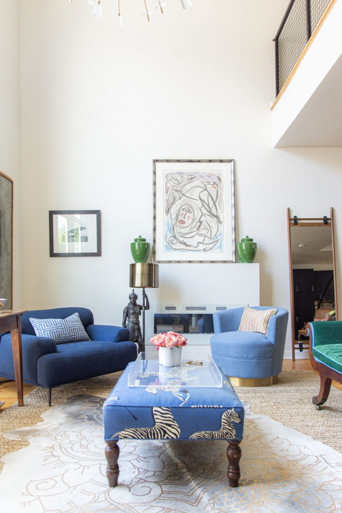 Double-story living room with blue sofa, green chaise, cowhide rug, Article Abisko chair, and sputnik chandelier by Kevin O'Gara on Thou Swell #livingroom #livingroomdesign #homedecor #interiordesign #homedesign #homedecorideas