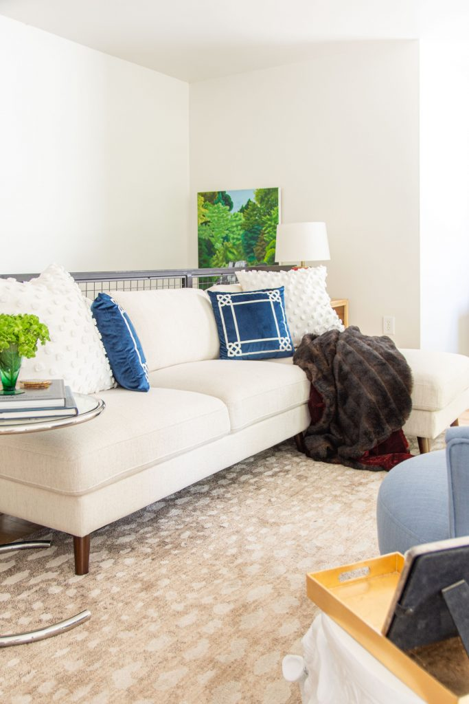 Blue velvet throw pillows with fur throw on beige sectional from At Home by Kevin O'Gara on Thou Swell #livingroom #sectional #homedecor #homedecorideas