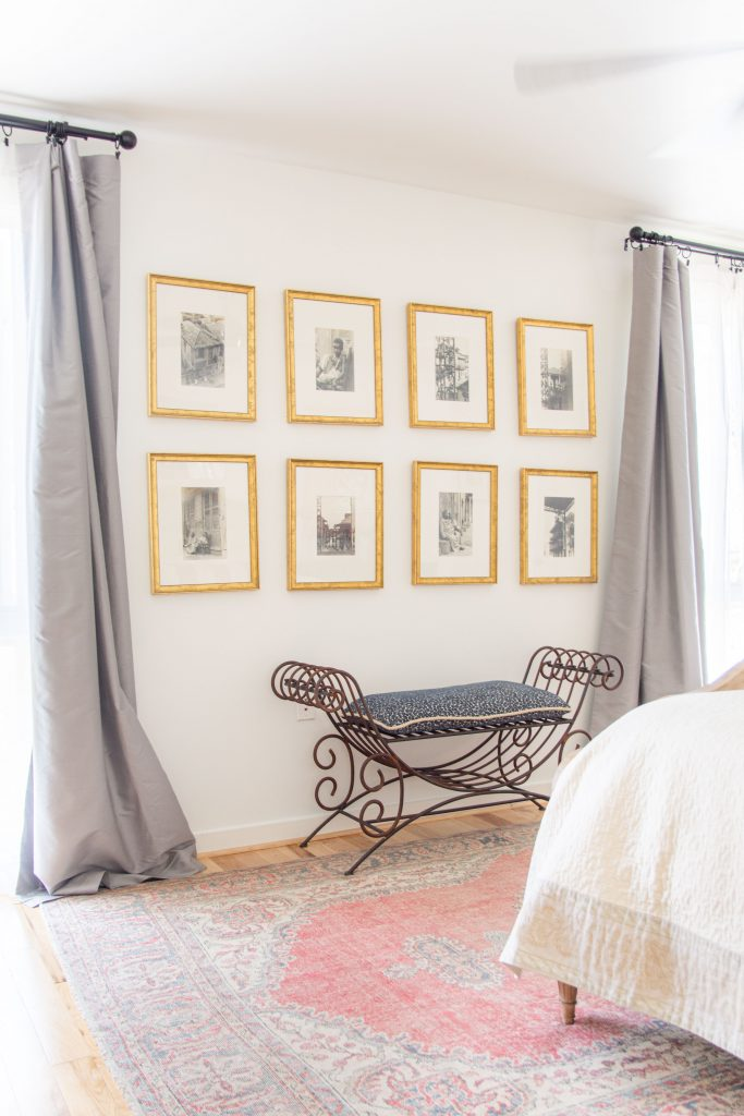 Black-and-white gallery wall ideas with gold frames, antique Italian bench, grey curtains in bedroom design by Kevin O'Gara on Thou Swell #gallerywall #goldframes #antiques #bedroom #bedroomdesign